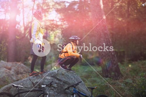 Biker couple looking at a view in forest