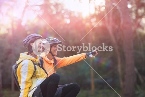 Side view of biker couple sitting and pointing in distance