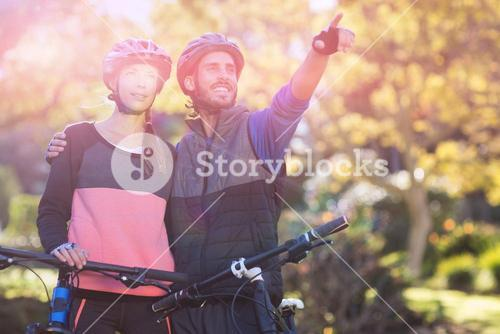 Biker couple with mountain bike pointing in distance