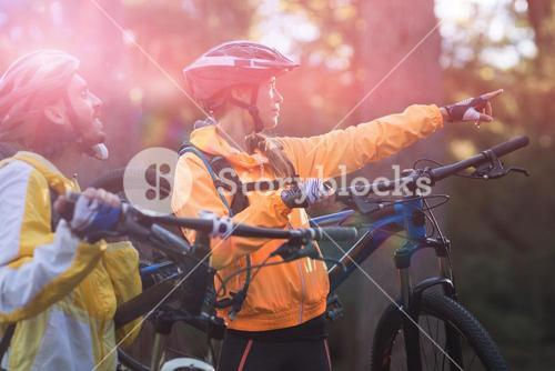 Biker couple carrying mountain bike and pointing in distance