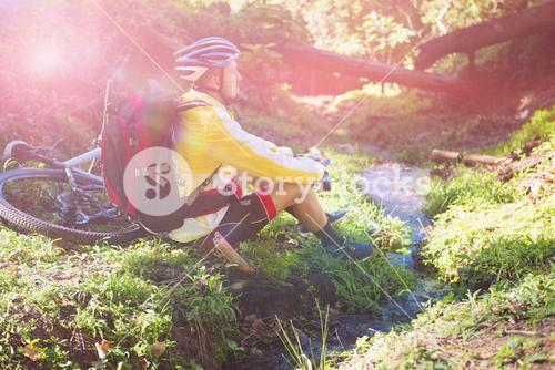 Mountain biker sitting near stream and looking at nature