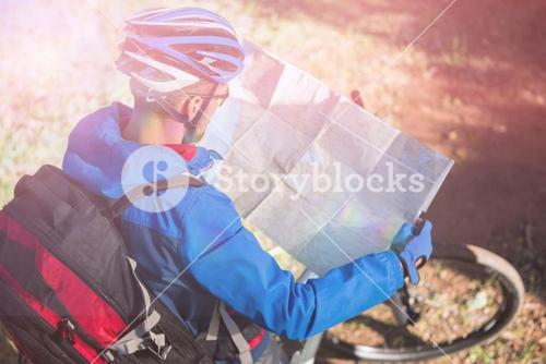 High angle view of male mountain biker looking at map