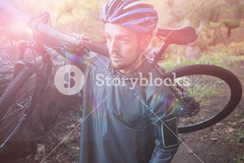 Male mountain biker carrying bicycle in forest