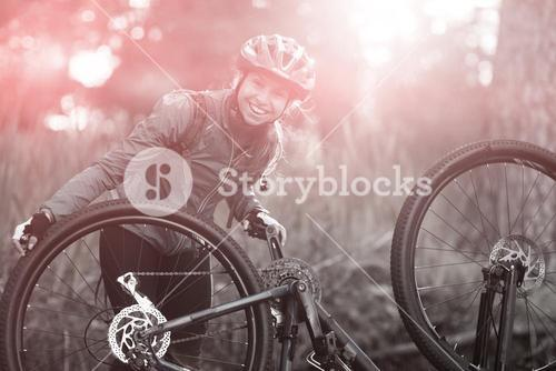 Portrait of female biker repairing mountain bike