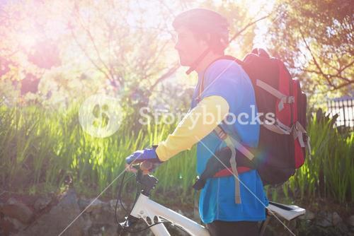 Side view of male mountain biker with bicycle in forest
