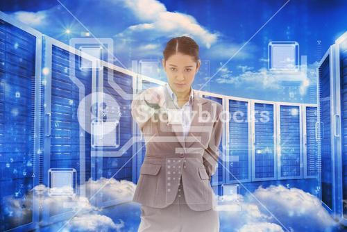 Composite image of portrait of a serious businesswoman pointing at the viewer