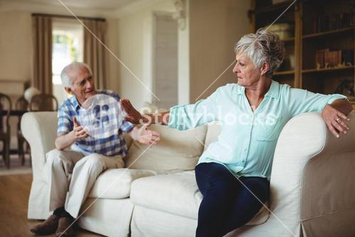 Upset senior couple in to an argument in living room