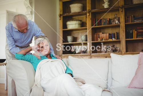 Senior man comforting senior woman in living room