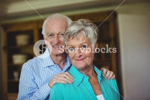Senior couple smiling in living room