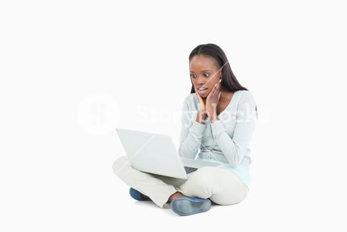 Young woman on the floor cannot believe whats on her screen