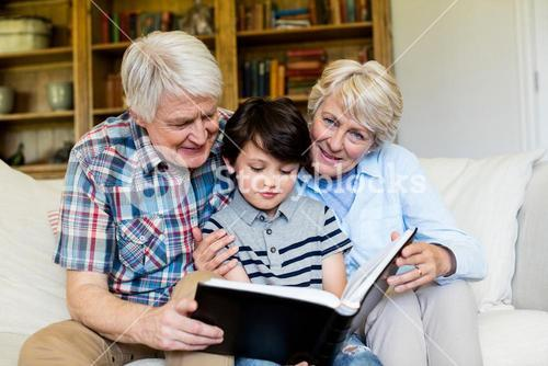 Grandparents and grandson looking at photo album in living room