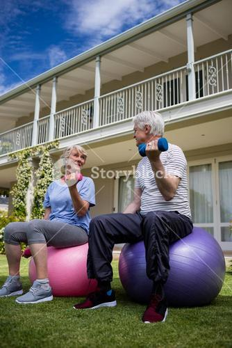 Senior couple interacting while exercising with dumbbells