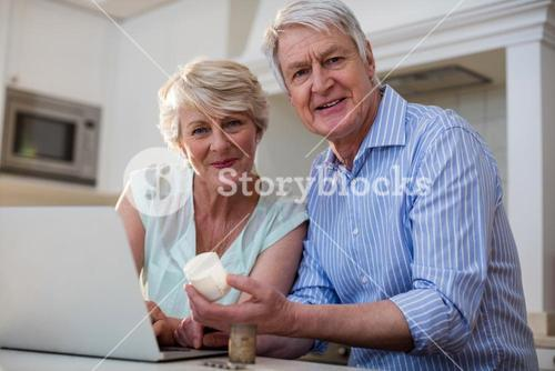Portrait of senior couple checking medicine on laptop in kitchen