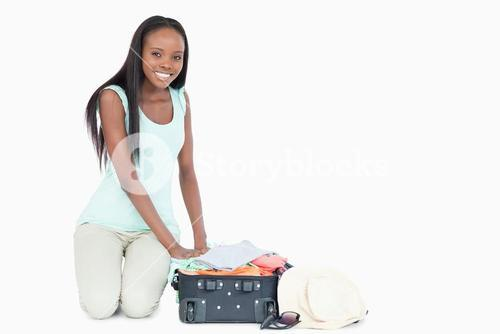 Young woman packing her suitcase