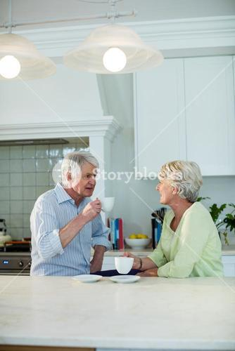 Senior couple having coffee at dining table