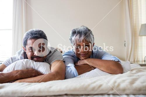 Portrait of happy senior couple lying on bed in bed room