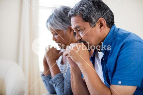 Tensed senior couple in living room