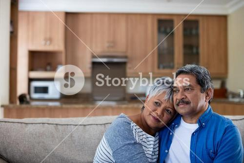 Thoughtful senior couple embracing each other on sofa in living room