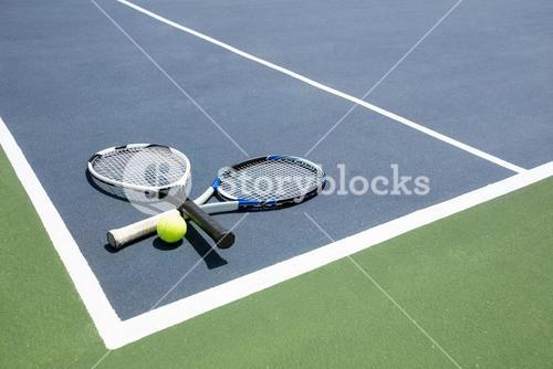 Tennis racquets and ball in court