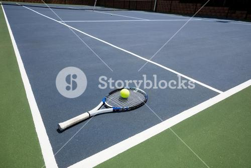 Tennis racquet and ball in court