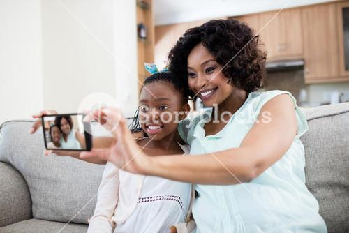 Mother and daughter tacking selfie on mobile home in living room