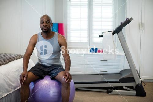 Portrait of man sitting on fitness ball in bedroom