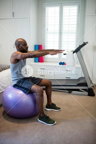 Man exercising on fitness ball in bedroom