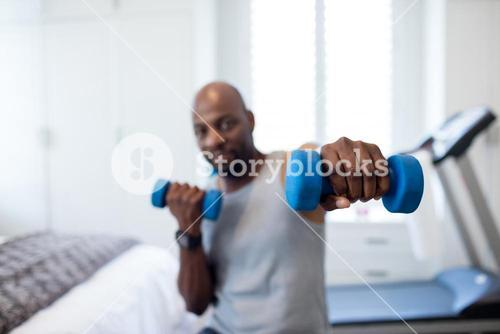 Man exercising with dumbbells in bedroom