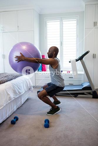 Man exercising with fitness ball in bedroom