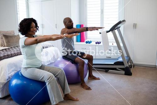 Couple exercising on fitness ball in bedroom