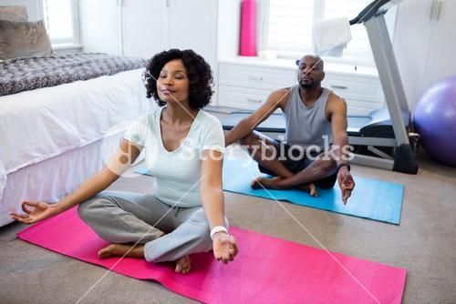 Couple meditating at home