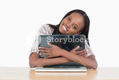 Young woman hugging her laptop