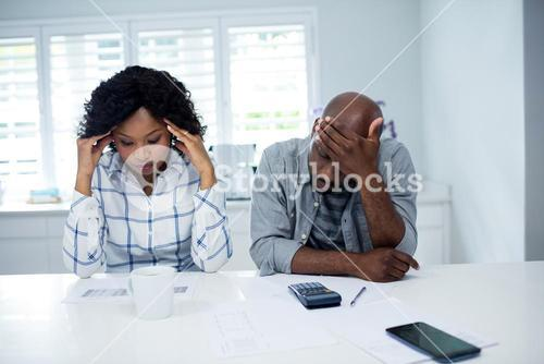 Worried couple checking the bills