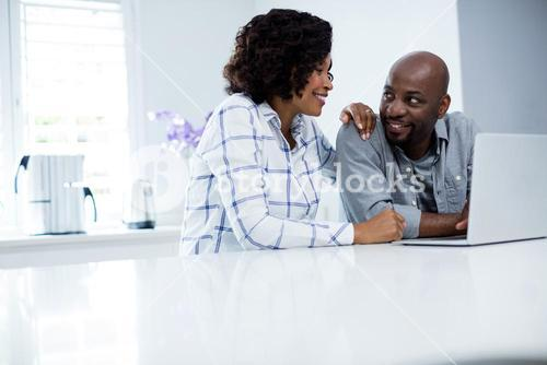 Happy couple interacting with each other while using laptop
