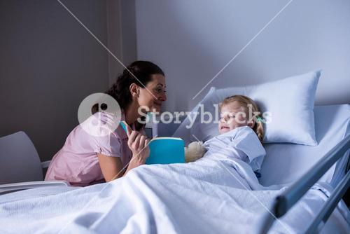 Girl on a hospital bed reading book with her mother