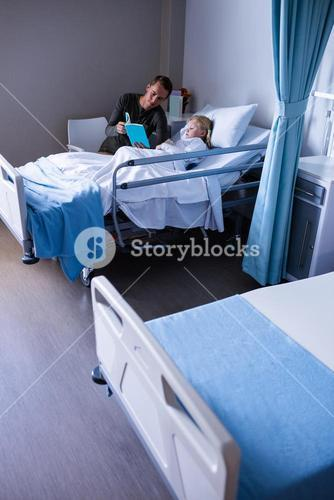 Girl on a hospital bed reading book with her father