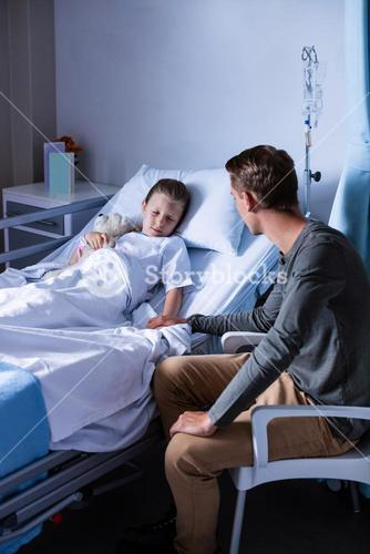 Father sitting beside her daughter lying on a hospital bed