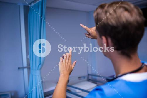 Rear view of doctor gesturing in ward