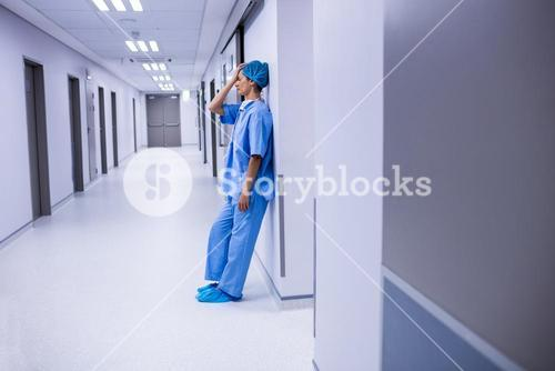 Sad surgeon leaning on wall in corridor