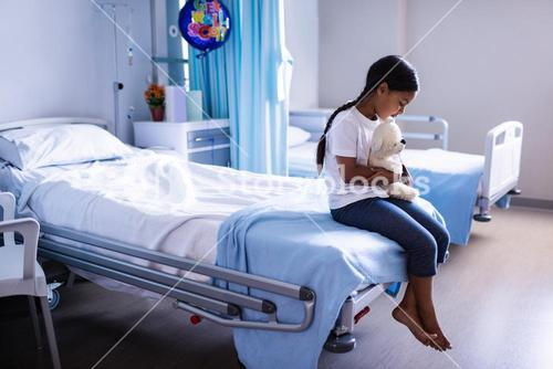 Patient sitting on bed with teddy bear