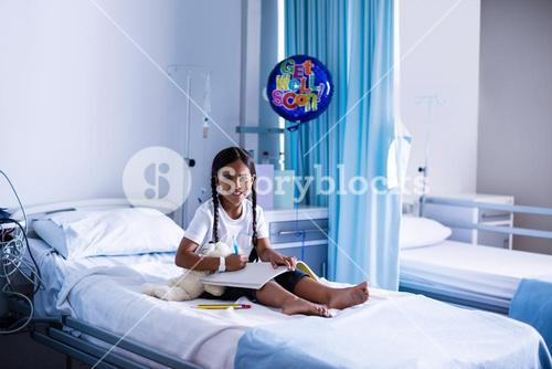 Smiling girl drawing picture in a book
