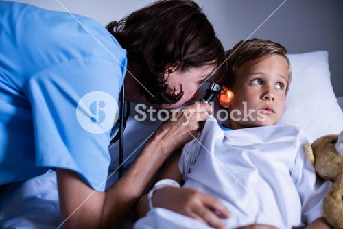 Female doctor examining patient ear with otoscope