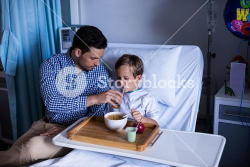 Father feeding breakfast to his son