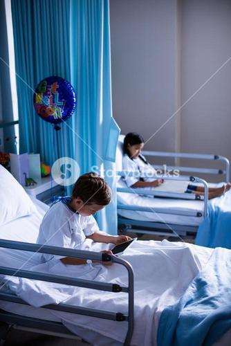 Patients with digital tablet and book sitting on bed