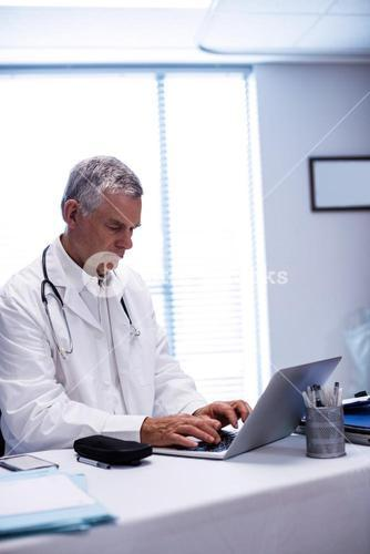Doctor sitting at table and using laptop