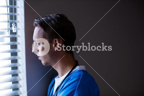 Thoughtful doctor looking through window