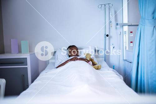 Patient sleeping with teddy bear on the bed
