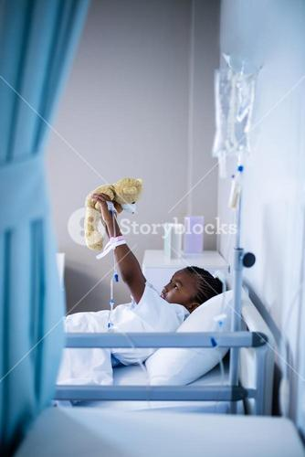 Patient playing with teddy while resting on the bed