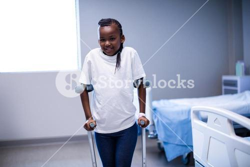 Portrait of girl walking with crutches in ward