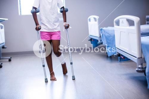 Girl walking with crutches in ward